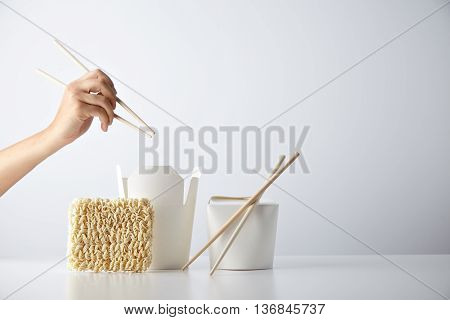 Hand with chopsticks ready above opened and closed takeaway boxes, brick of japanese egg noodles presented with chopsticks, isolated on white Retail set