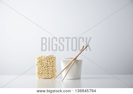 Brick of dry japanese noodles presented near closed blant retail takeaway box with chopsticks, isolated on white