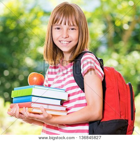 Outdoor portrait of happy girl 10-11 year old with books and apple. Back to school concept.