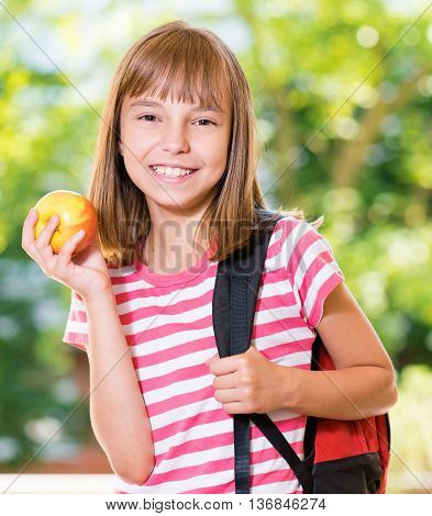Outdoor portrait of happy girl 10-11 year old with apple and backpack. Back to school concept.