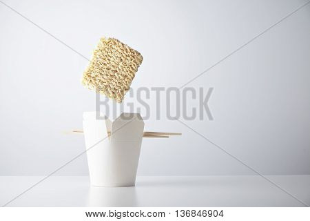 Brick of dry noodles falls down inside blank takeaway box with chopsticks isolated on white commercial retail set