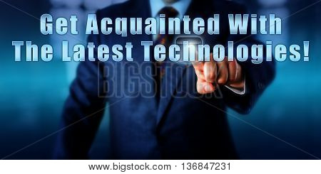 Manager pushing the sentence Get Acquainted With The Latest Technologies! onscreen in mid air. Business concept motivational metaphor and call to action. Close up torso shot of a man in blue suit.