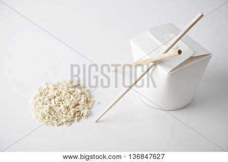 Closed blank takeaway noodles box with chopsticks near dry pasta in circle shape isolated on white close focus commercial presentation mockup