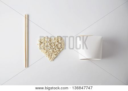 Top view I love wok takeaway noodles presentation with chopsticks, blank box and dry pasta isolated on white