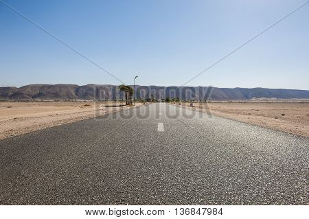 Closeup of a tarmac road surface going into the distance through the desert