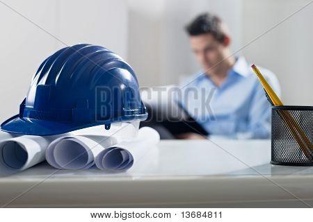 Bauarbeiterhelm und Blueprint auf Schreibtisch, mit Architekten im Hintergrund