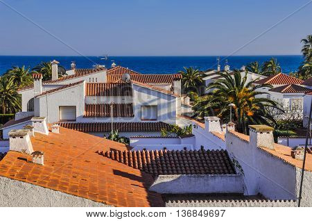 View on housetops from terracotta tiles palm trees blue sea. Travel destination. Costa Dorada Spain. Horizontal.