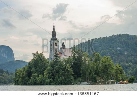beautiful island with church on lake Bled with forest background