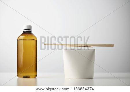Retail takeaway presentation business set: plastic brown bottle with water on left side of closed blank box with wok noodles inside and chopsticks on top isolated on white closeup mockup
