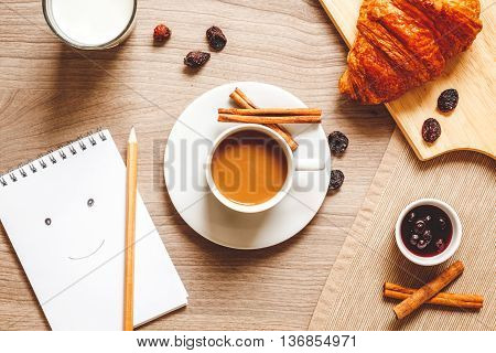 breakfast at home on wooden table with cup of milk coffee, croissants, macaroon, crackers and notebook top view