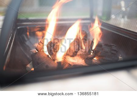 Firepit in the middle of a fire table, burning coals with flames