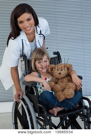 Smiling Little girl on a wheelchair holding her teddy bear