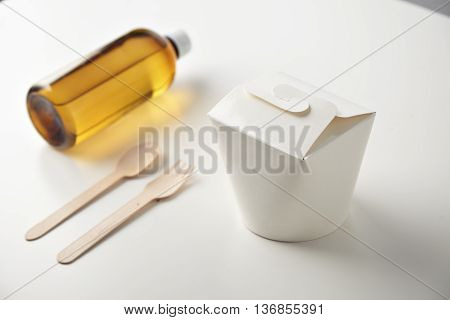 Commercial retail takeaway promo, top view simple set, plastic brown bottle with drink, closed blank wok box and recycled eco friendly spoon and fork presented isolated on white side view mockup