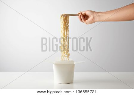 Hand picks up tasty boiled noodles from opened wok takeaway blank paper box isolated on white in center mockup