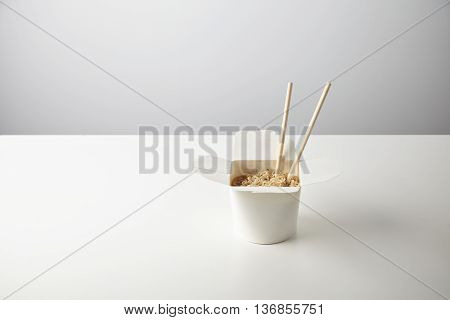 Tasty noodles with soy sause and spices inside blank takeaway paper wok box isolated on white with chopsticks inside