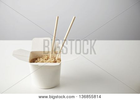 Tasty noodles with soy sause and spices inside blank takeaway paper box with chopsticks inside isolated on white