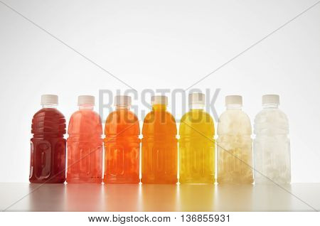 Drinks from coconut cream and milk mixed with fruits and berries inside small plastic bottles presented on white Healthy refreshment sweet drink mockup