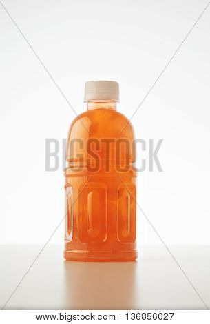 One takeaway bottle with drink from coconut cream and milk mixed with fruits and berries isolated on white Healthy refreshment sweet drink mockup