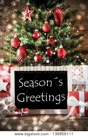 Christmas Card For Seasons Greetings. Christmas Tree With Balls And Snowflakes. Gifts Or Presents In The Front Of Wooden Background With Bokeh Effect. Chalkboard With English Text Seasons Greetings