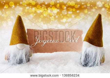 Christmas Greeting Card With Two Golden Gnomes. Sparkling Bokeh And Noble Background With Snow. French Text Joyeux Noel Means Merry Christmas