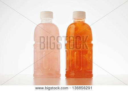 Takeaway bottles with drink from coconut cream and milk mixed with fruits and berries isolated on white Healthy refreshment sweet drink with lychee and papaya bites inside. mockup