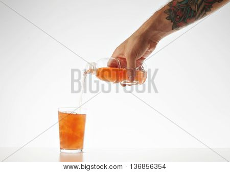 Hand pours from takeaway bottle drink from coconut cream and milk mixed with fruits and berries isolated on white Healthy refreshment sweet drink with watermelon bites inside.