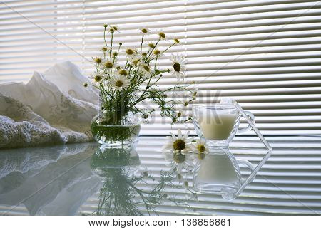 a bouquet of daisies in a glass vase, cup of milk and lace sundress on a table on a background window. still life in white