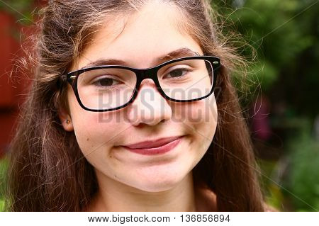 teen girl with short sight glasses and brown thick hair close up portrait on the summer green background