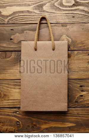 Brown takeaway bag from thic recycled craft paper on rustic wooden table mockup