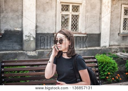 Young and beautiful girl talking on the phone in the city center.