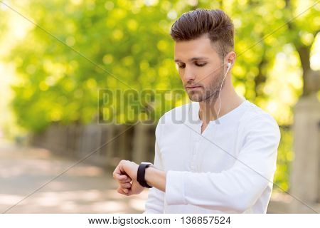Skillful male jogger is looking at tracker on his arm with seriousness. Man is listening to music from earphones. He is standing outdoors