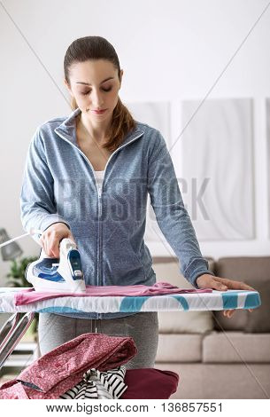 Confident young woman at home ironing her clothes on the ironing board housekeeping and chores concept