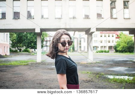 A young girl with beautiful hair and dress a black shirt waiting for friends. She straightens hair at school. Pretty Girl. Wind develops hair