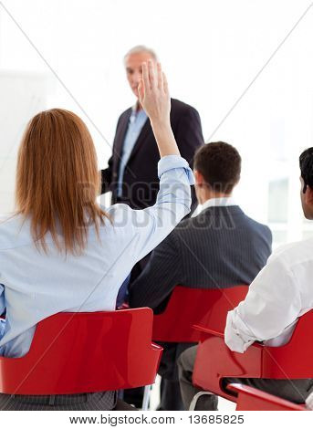 Businesswoman raising her hand up at a conference. Business concept.