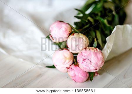 Bouquet of pink peonies in kraft paper on wooden floor