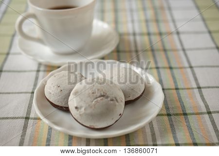 White cake in the foreground and a Cup of coffee