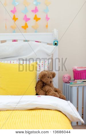 Close-up of child's bedroom with a teddy bear on the bed