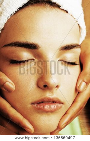stock photo attractive lady getting spa treatment in salon, close up asian hands on face green towel
