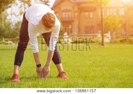 Healthy young man is exercising in park. He os standing and bending his torso with arms down. Copy space in right side