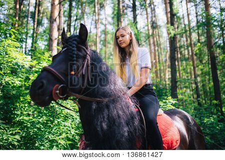 Yong girl in the Woods ride on black horse.
