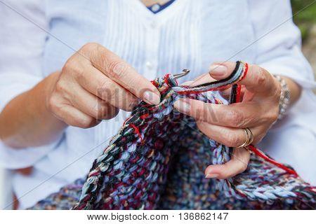 skiled women hands crochet multicolored woolen carpet