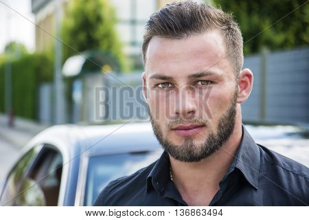 Headshot of young bearded man leaning on his new stylish polished car outdoor, looking at camera