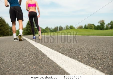 Skillful two runners competing on road. Focus on their back