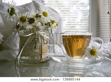 cup of tea, lace sundress, and a bouquet of daisies on a background of the summer window.