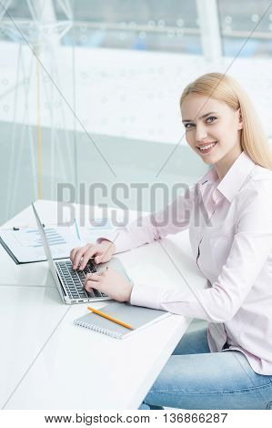 Love my job. Portrait of young office worker sitting at her workstation in office