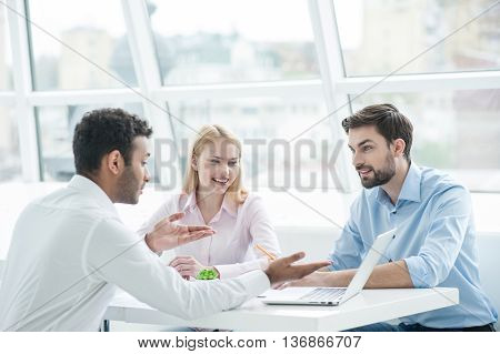 Great minds getting together. Confident young African man pointing laptop while sitting together with his colleagues in office