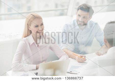 In brainstorming zone. Smiling young woman having brainstorming session in modern office