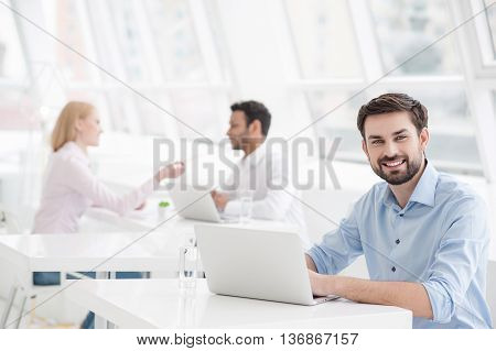 I work for best company. Businessman sitting in modern office and working at laptop with colleagues in background