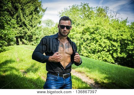 Handsome Hunk Man Outdoor in City Park, Opening his Shirt to Show Muscular Torso and Chest During Daytime, Wearing Black Shirt and Sunglasses