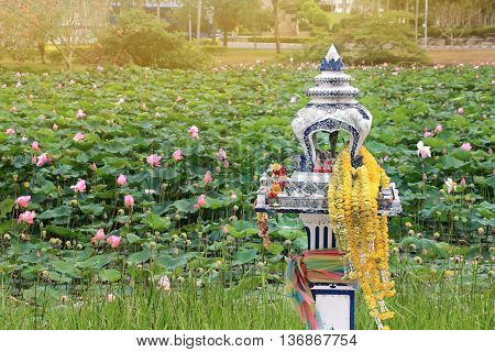 spirit house in thailand with flowers in vases and some wreathes house joss